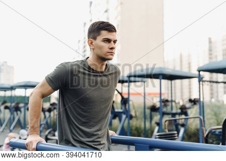 Strong Muscular Young Man Is Working Out In Gym Outdoor. Closeup Of Young Strong Teenage Athlete Doi