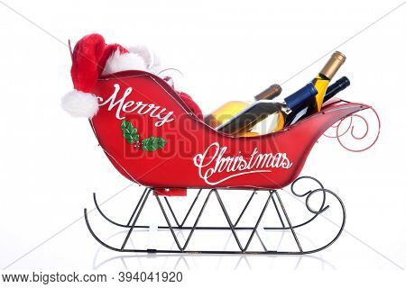 Christmas Wine. A Christmas Sleigh is filled with bottles of Wine, Wine Glasses and a Santa Hat. Isolated on white. Room for text.