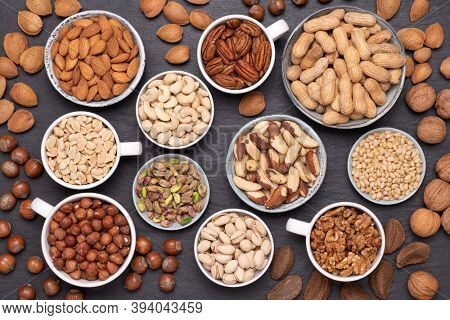 Assortment of various nuts in bowls and cups, top view on black, stone background