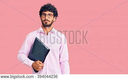 Handsome young man with curly hair and bear holding business folder thinking attitude and sober expression looking self confident