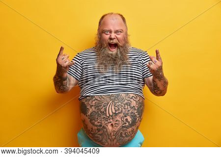 Indoor Shot Of Overweight Rock Fan Gestures Actively And Shouts, Enjoys Favorite Music, Keeps Mouth