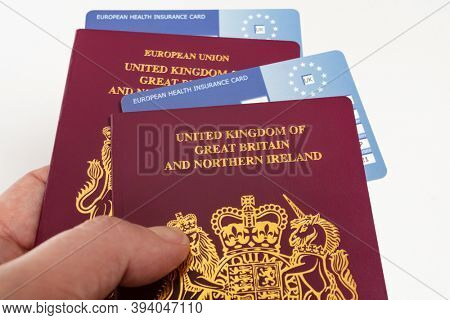 Hand holding United Kingdom British passports and EHIC European Union Health Insurance Cards.