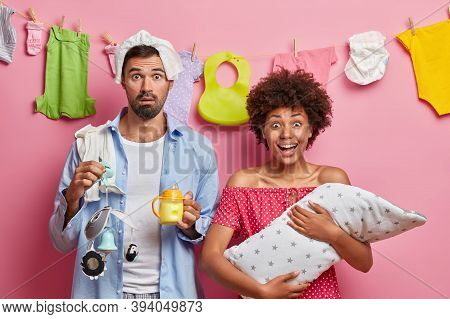 Photo Of Happy Dark Skinned Mother Holds Small Baby Wrapped In Blanket, Shocked Father With Nappy On