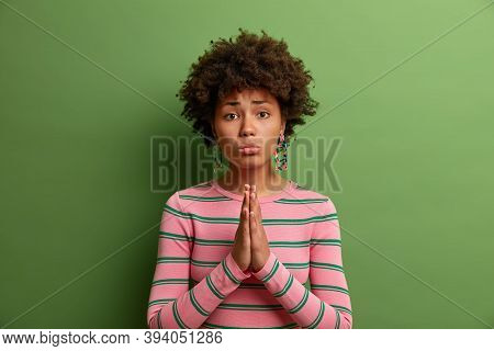 Please, I Need It Very Much. Sad Dark Skinned Female With Imploring Look, Clasps Palms Together, Pra