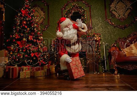 Santa Claus brought gifts for Christmas. He stands in a night room  with beautiful Christmas tree and fireplace. Christmas and New Year concept.