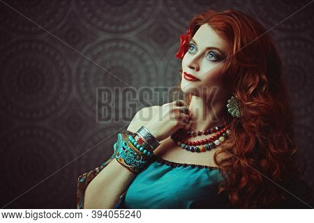 Portrait of a beautiful red-haired gypsy woman. National gypsy costume, ethnic. Make-up and hairstyle.