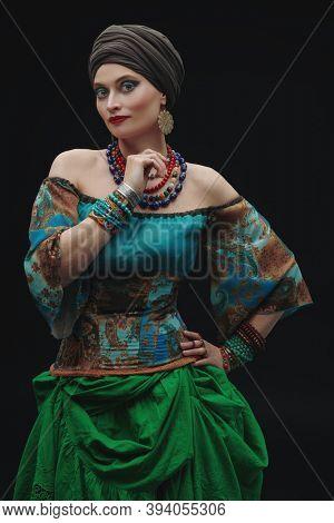 Portrait of a beautiful gypsy woman on a black background. Studio shot. National gypsy costume, ethnic.
