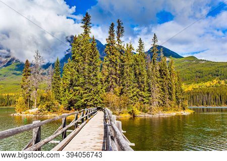 Rocky Mountains of Canada. Pyramid Lake. Narrow wooden bridge connects a small wooded islet with the lake shore. Active eco and photo tourism concept