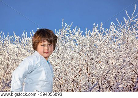 New Years is soon. Handsome boy in judo uniform training for judo. Frosty snowy sunny day in the winter forest
