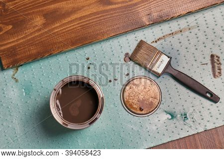 Painting lumber with wood stain coloring with paint brush