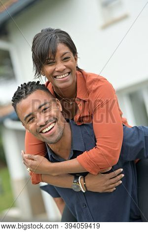 Portrait of happy african-american couple standing outside the house