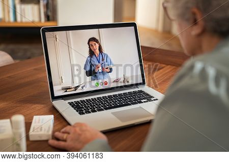 Old woman using laptop in an online consultation with her doctor during home quarantine. Senior woman at home having video call on computer with physician during covid-19 outbreak.