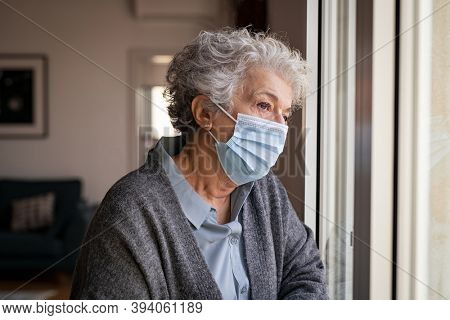 Lonely old woman wearing surgical mask. Sad senior lady wearing face protective medical mask and looking through the window. Alone depressed woman stay at home during quarantine due to the coronavirus