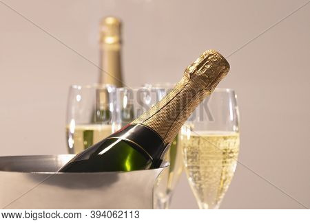 Select Focus Of A Champagne Bottle Inside A Champagne Bucket With Out Of Focus Champagne Glasses And