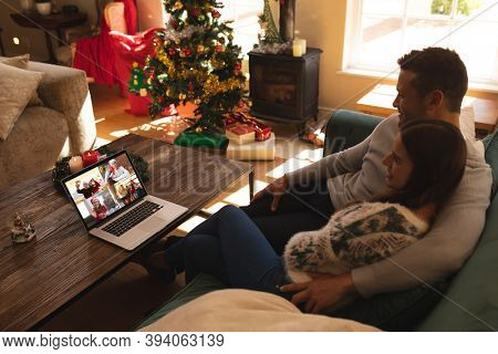 Caucasian couple at christmas, sitting on sofa at home embracing having video chat with friends and family on laptop screen. social distancing during covid 19 pandemic at christmas time.