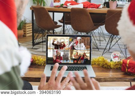Caucasian couple at christmas, having video chat with friends and family using laptop, sitting at home wearing santa hats and waving. social distancing during covid 19 pandemic at christmas time.