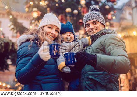 Family with child having fun at the Christmas market enjoying the season