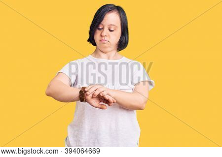 Brunette woman with down syndrome wearing casual white tshirt checking the time on wrist watch, relaxed and confident