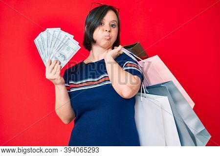Brunette woman with down syndrome holding shopping bags and dollars puffing cheeks with funny face. mouth inflated with air, catching air.