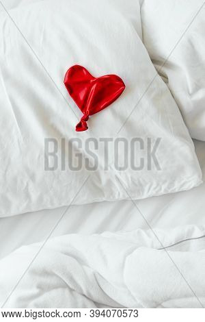 Red Deflated Ball On A Pillow On White Bedding. Valentines Day Concept.
