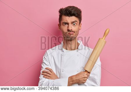 Indoor Shot Of Male Cook Looks With Displeased Sullen Expression, Holds Rolling Pin, Feels Tired Aft