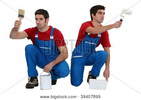 Two male decorators working in unison