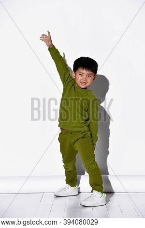 Fashion Portrait Of A Cute Little Boy In A Stylish Green Tracksuit Against A White Studio Wall Backg