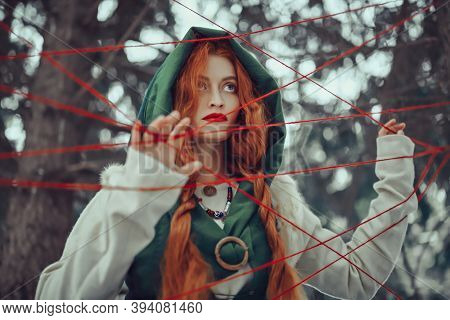 The medieval sorceress and the threads of fate in the thicket of the winter forest. Historical reconstruction of the Middle Ages. Fairy tales.