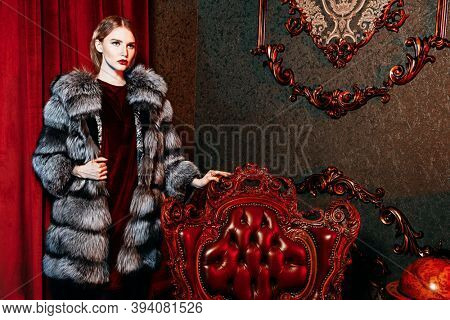 Fur coat fashion. Portrait of a gorgeous fashionable woman posing in a silver fox fur coat in a luxury apartment.