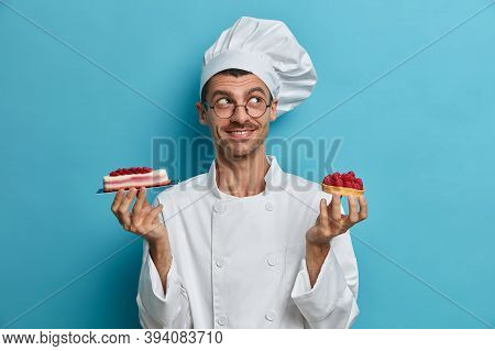 Confectioner Man Stands With Delicious Cakes, Has Nice Ideas How To Decorate Pastry, Poses Against B