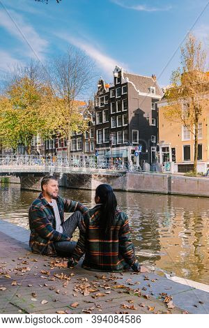 Amsterdam Netherlands During Autumn Fall Season , Couple Men And Woman Visit The Cituy Of Amsterdam