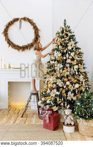A Ten-year-old Girl Is Decorating A Christmas Tree. Children, Family And Holiday Concept. Christmas
