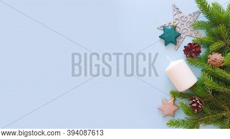 Fir Frame, Christmas Stars, White Candle And Pine Cones On Pastel Blue Background. Top View Of Chris