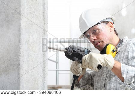 Man Using An Electric Pneumatic Drill Making A Hole In Wall, Professional Construction Worker With S