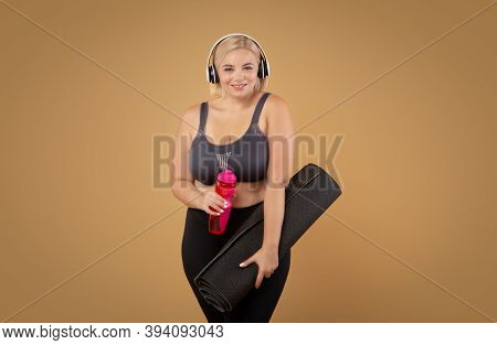 Body Positive And Sport. Curvy Plus Size Woman In Sportswear Holding Fitness Mat And Bottle With Wat