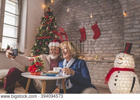 Senior Couple Having Fun While Having Virtual Party With Friends And Family On Christmas Day; Elderl