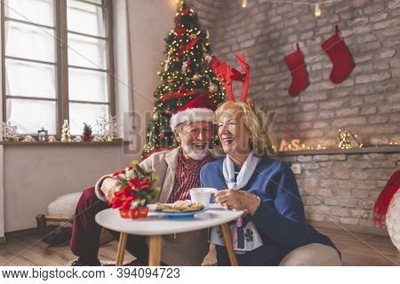 Cheerful Senior Couple Sitting By Nicely Decorated Christmas Tree, Having Fun While Drinking Coffee