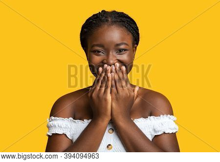 Laughter. Cheerful Black Lady Smiling And Covering Mouth With Hands In Happy Excitement, Emotionally