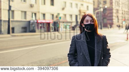 Redhead Woman In Grey Coat And Black Protective Mask Standing On An Empty Sunny Street. End Of Covid