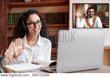 Online Tutoring. Portrait Of Woman In Glasses And Headset Having Video Conference, Sitting At Desk A