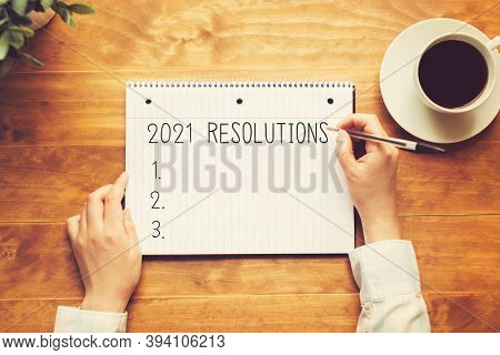 2021 Resolutions With A Person Holding A Pen On A Wooden Desk