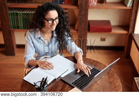 High Angle View Portrait Of Smiling Young Woman Sitting At Desk, Typing On Keyboard And Using Laptop