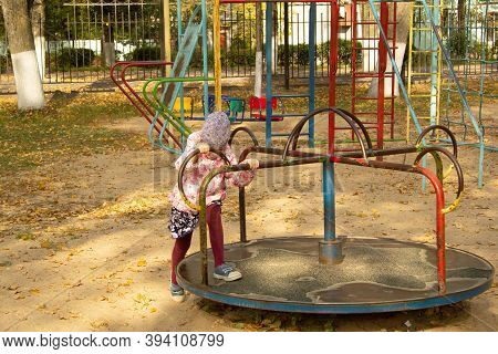 A Five-year-old Girl Tries To Unwind On The Carousel Turntable In The Fall. Playground.