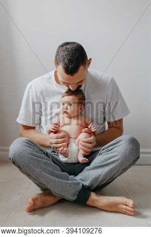 Happy Caucasian Father Holding Newborn Baby On Laps Knees. Man Parent Embracing Playing With Child D
