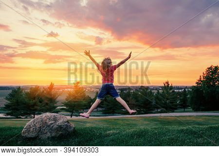 Cute Child Jumping Up With Her Arms Raised On Hill At Sunset.  Girl Kid Having Fun Outdoor Enjoying