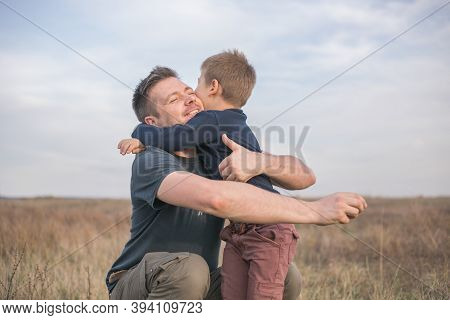 Happy Son Hugging Dad On The  Meadow Background. Concept Of Father-son Relationship. Proud Father Hu