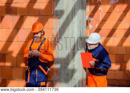 Workers In Helmet. Two Repairman On Construction. Advertising. Repairman. Hammer. Spanner. Wrenches.
