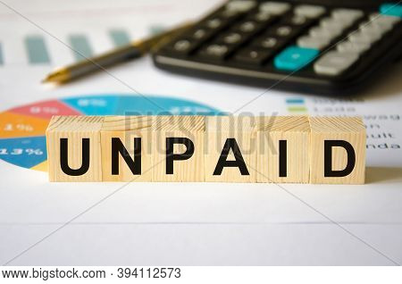 The Word Unpaid Is Written On A Block Of Wood. Unpaid Text On Wooden Cubes Calculator In The Backgro