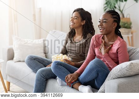 Two Black Girlfriends Having Fun At Home, Watching Comedy And Eating Popcorn, Copy Space. Laughing A