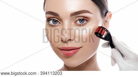 Beautiful Woman During Microneedling Procedure. Beautician Doing Female Skin Treatment Using A Micro